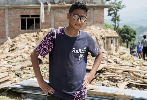 Pojke vid förstörd skola i Sindupalchok