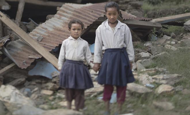 Systrar utanför förstörd skola