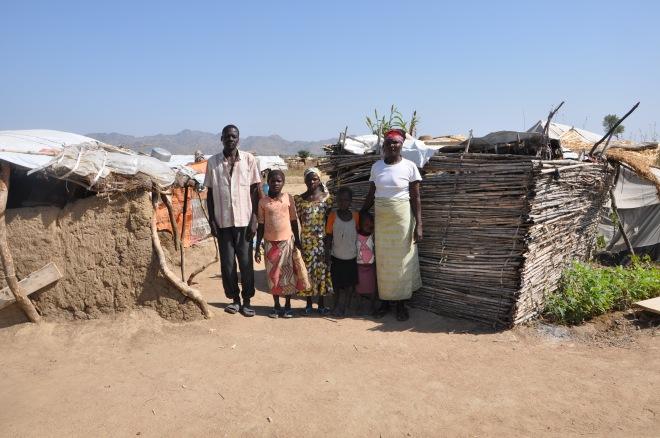 Familj framför sitt hus i flyktinglägret Minawao.