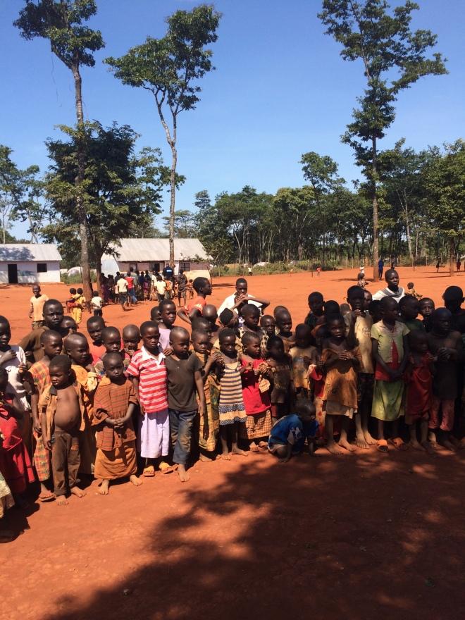 Barnen samlas under rasten i den barnsäkra platsen i Mtendeli för att observera sina besökare noggrant.
